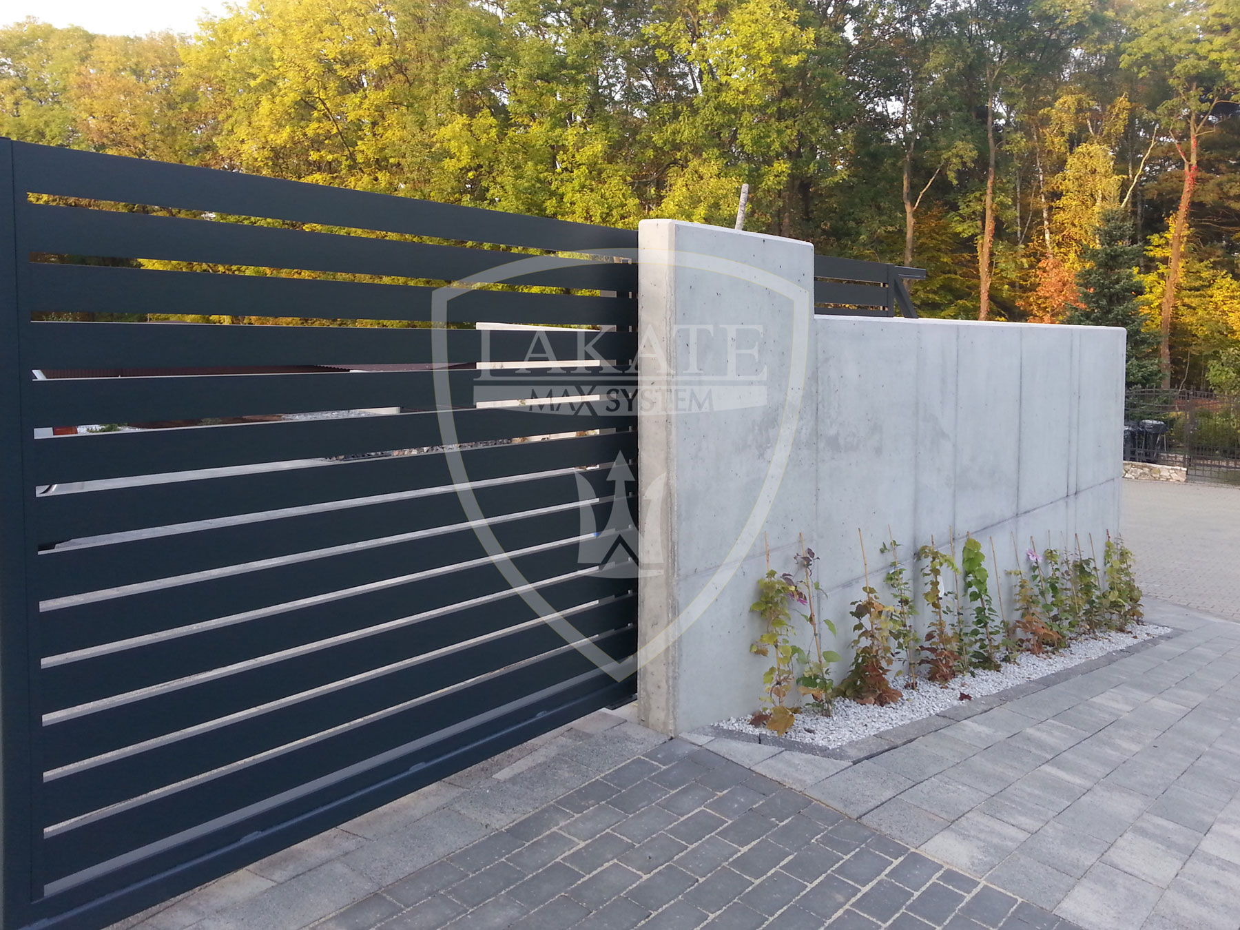 Brama przesuwna lakate osadzona na betonie architektonicznym